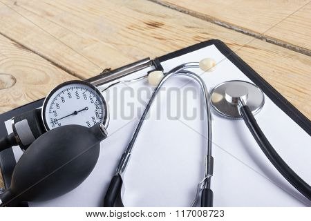Medical clipboard and stethoscope on wooden desk background. Top view. Workplace of a doctor.
