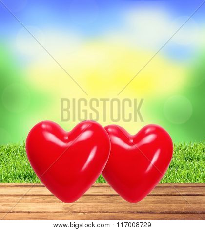 Two Red Hearts On Wooden Table, Blurred Nature Background And Green Grass