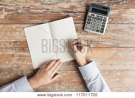 close up of hands with calculator and notebook