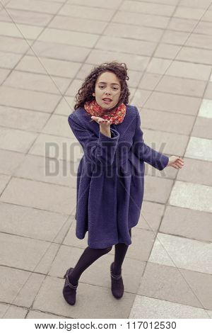 Woman Sends A Kiss, Standing On A Stone Tile Street