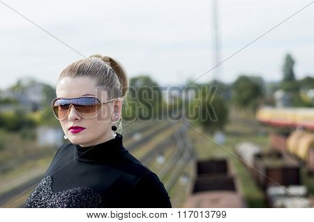 Portrait Of The Beautiful Woman Against The Train And Railway Tracks