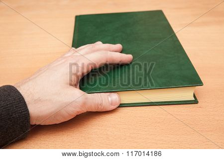 Male Hand And Book With Empty Dark Green Cover