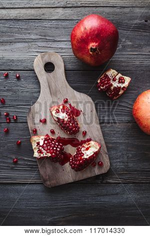 A cut pomegranate with seeds on a board