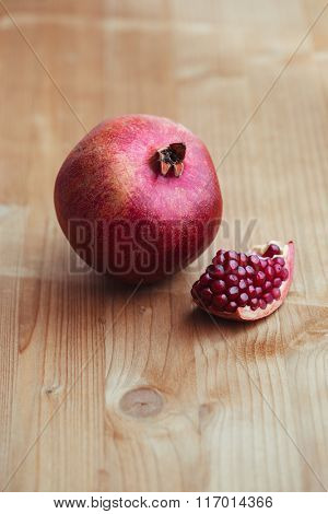 Cut and whole pomegranate on wooden table