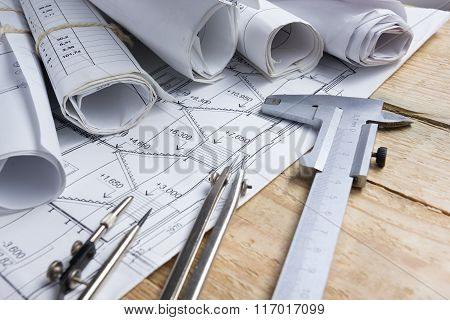 Architectural project, blueprints, blueprint rolls and divider compass, calipers on vintage wooden b