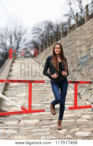 Beautiful girl wearing leather jacket, blue jeans and boots