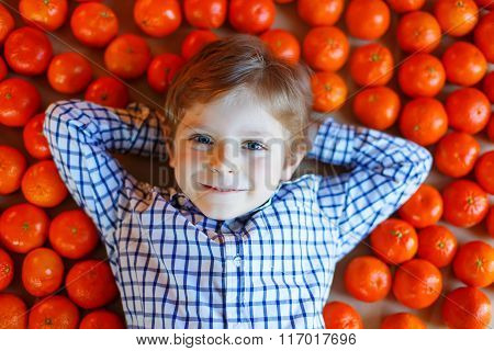 Little kid boy with healthy mandarin oranges fruits
