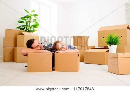 Moving To A New Apartment. Tired Family Couple And Cardboard Boxes.