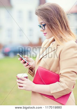 Attractive  young business woman wearing glasses holding a smartphone, bag and take away coffee standing outdoor in the street. Communication texting internet browsing concept.
