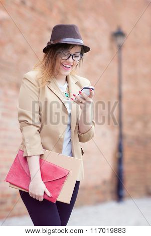 Young attractive happy student woman wearing hat and glasses holding a briefcase using a smart phone in the street. Technology internet browsing communication  and social media concept.