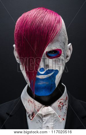 Clown And Halloween Theme: Scary Clown With Pink Hair In A Black Jacket On A Dark Background In The