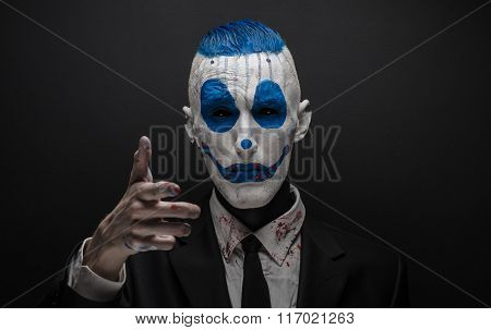 Terrible Clown And Halloween Theme: Crazy Blue Clown In Black Suit Isolated On A Dark Background In