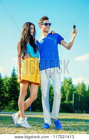 Happy young couple walking in the park and making selfie by smart phone. Happy summer day.