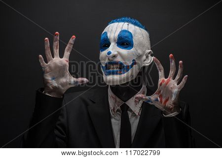 Terrible Clown And Halloween Theme: Crazy Blue Clown In Black Suit Isolated On A Dark Background