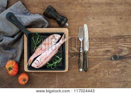 Raw uncooked Red Mullet fish in a cooking pan with rosemary, lemon and garlic over rustic wooden bac