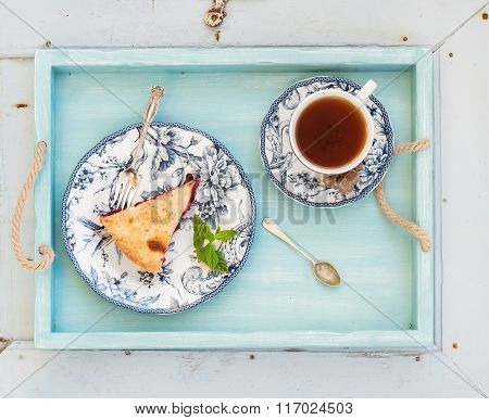 Piece of double crust plum pie and black tea in vintage porcelain cup, blue wooden tray. Top view, h
