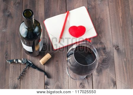 Red Wine Glass And Notebook On Table
