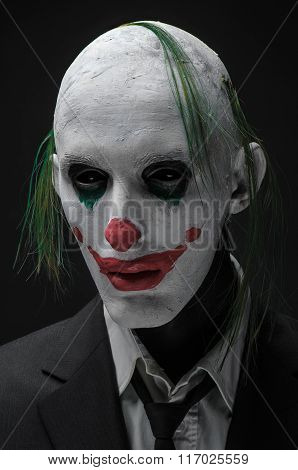 Terrible Clown And Halloween Theme: Crazy Terrible Green Clown In Black Suit Isolated On A Dark Back
