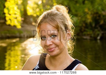 Portrait Of Beautiful Girl On Background Of Summer Park And The Bright Sun
