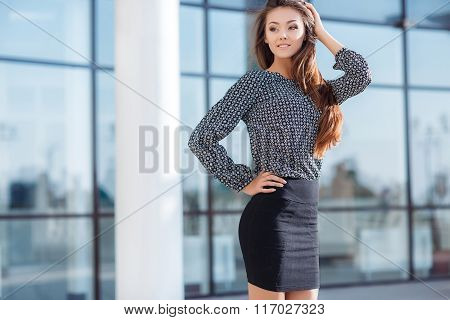 Portrait of a beautiful young woman standing near the glass building.