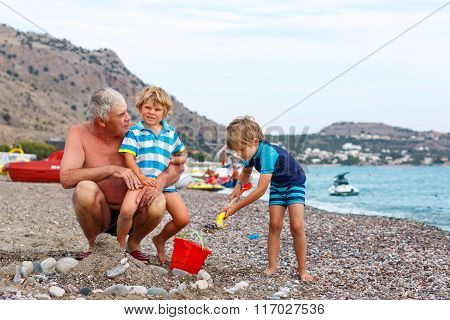 Grandfather and two little kid boys on ocean beach