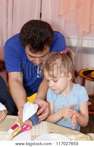 Father Helps His Daughter To Make Paper Crafts