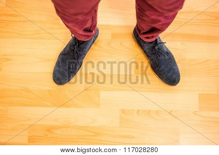 Above view of a man with black shoes on wooden park