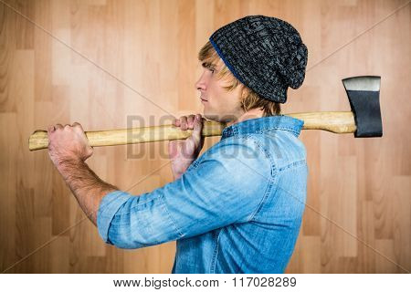 Side view of hipster standing with axe against wooden wall