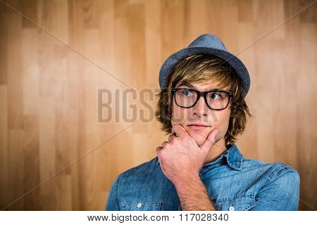 Close up of hipster man thinking with wooden background