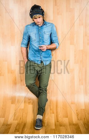 Focused hipster listening to music with wooden background