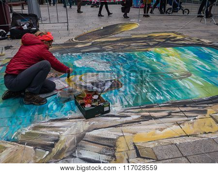 Street artist working a 3D painting