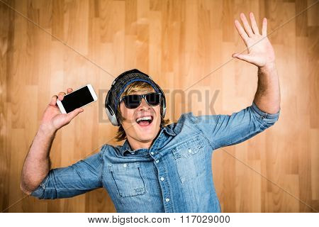 Cheerful hipster listening to music with hands up