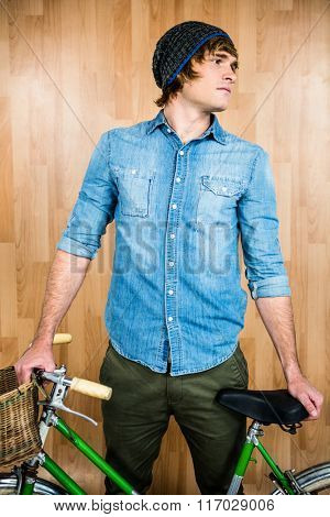 Portrait of hipster standing with bicycle against wooden wall