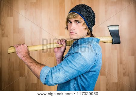 Profile of hipster standing with axe against wooden wall