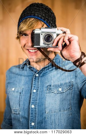 Smiling hipster man taking picture with digital camera
