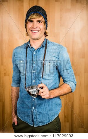 Smiling hipster man holding digital camera with wooden background