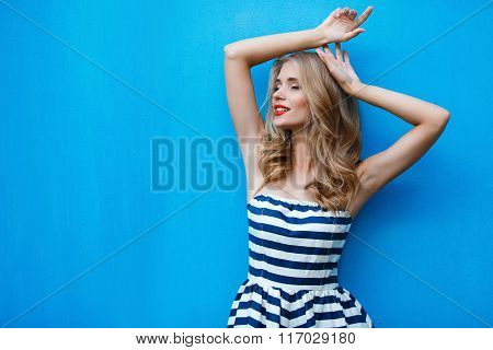 Summer portrait of young blonde on a blue background