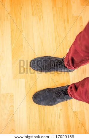 Above view of a man with black shoes on wooden plank