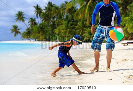father and son playing ball at beach