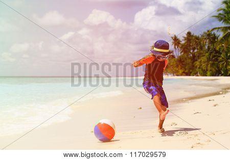 little boy playing ball at beach