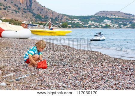 Little kid boy playing on beach with stones