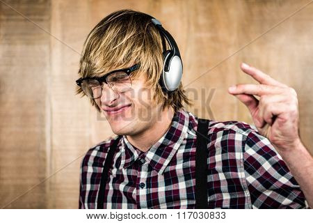 Cheerful blond hipster listening to music with wooden background