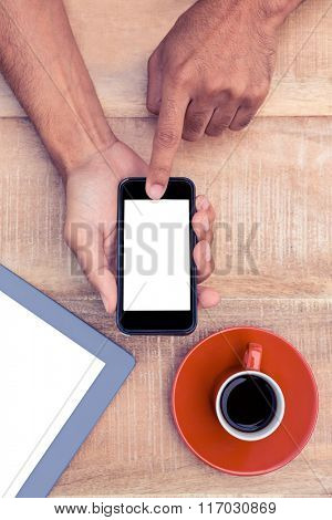 Cropped image of person using smart phone by coffee and tablet on table