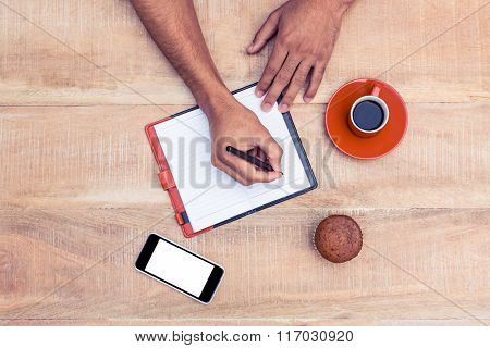 Cropped image of man writing on diary at table