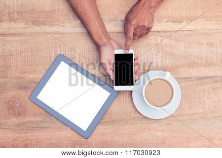 Directly above shot of person using smart phone by coffee and tablet on table