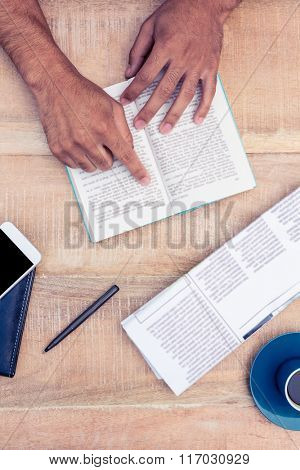 Cropped image of man reading book on table