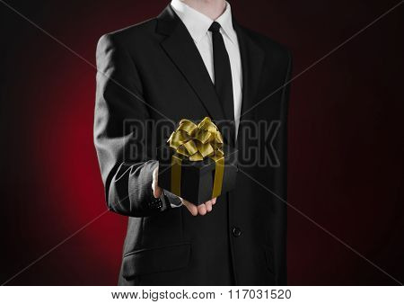 Theme Holidays And Gifts: A Man In A Black Suit Holds Exclusive Gift Wrapped In A Black Box With Gol