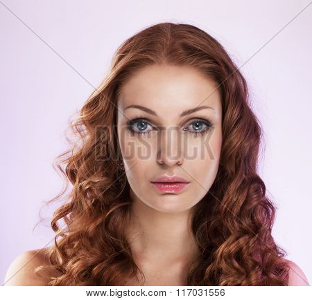 Beautiful woman with long curly hair on lilac background