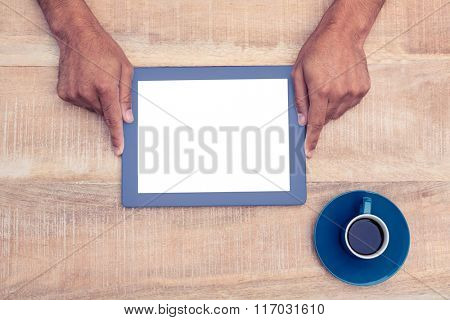 Directly above shot of hand holding on digital tablet over table by coffee