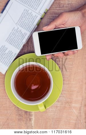 Cropped image of man holding smart phone by coffee and newspaper on table